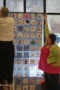 June assists in hanging a quilt at Great American in Cooperstown.