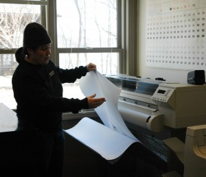 Abby prints the drawings on the plotter.